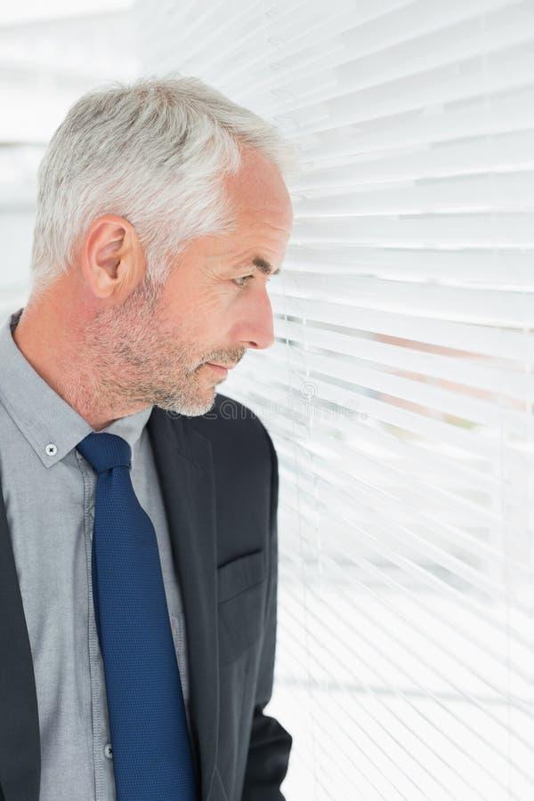 Серьезный зрелый бизнесмен peeking в офисе стоковые фото