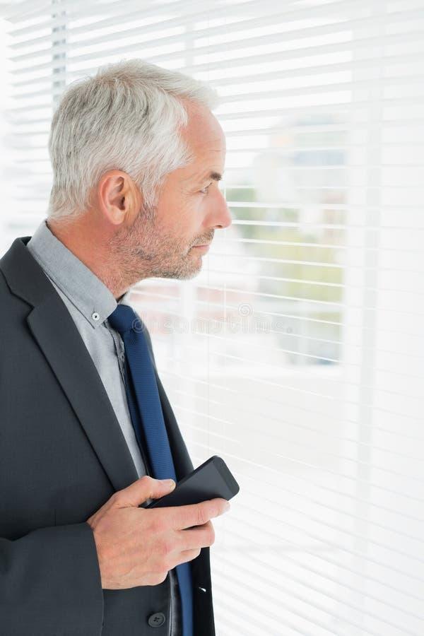 Серьезный зрелый бизнесмен peeking в офисе стоковые изображения rf