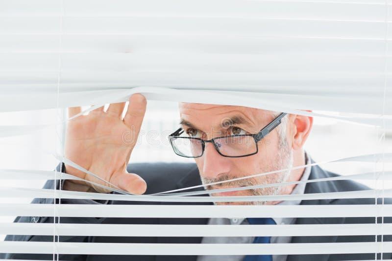 Серьезный зрелый бизнесмен peeking через шторки в офисе стоковое изображение