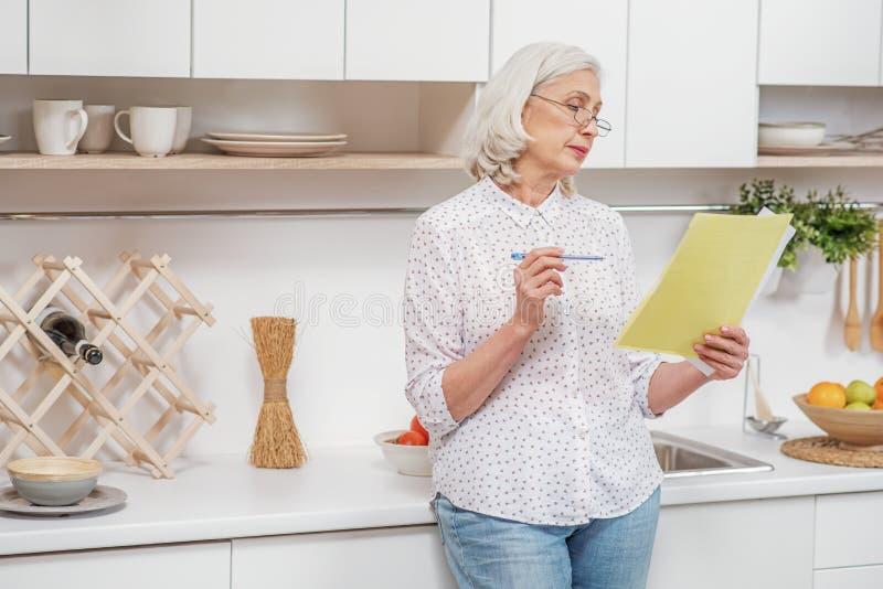 Серьезный зрелый документ чтения женщины дома стоковое изображение rf