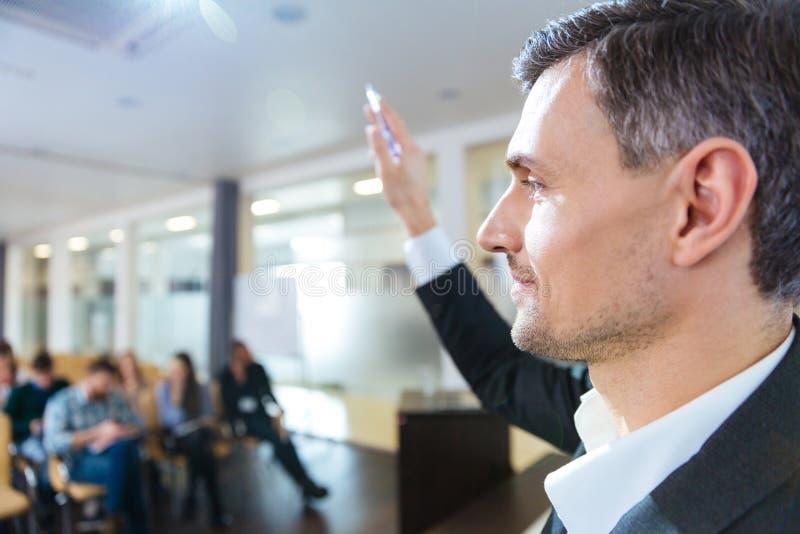 Серьезный диктор стоя с поднятой рукой на деловой встрече стоковые изображения rf