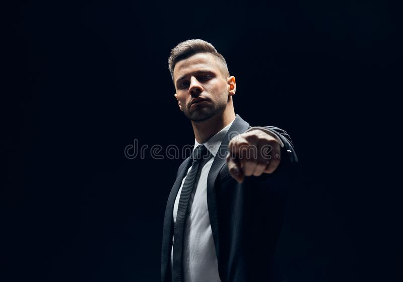 Серьезный красивый человек в черном костюме указывая его палец на вас и камера изолированная на темной предпосылке стоковые изображения