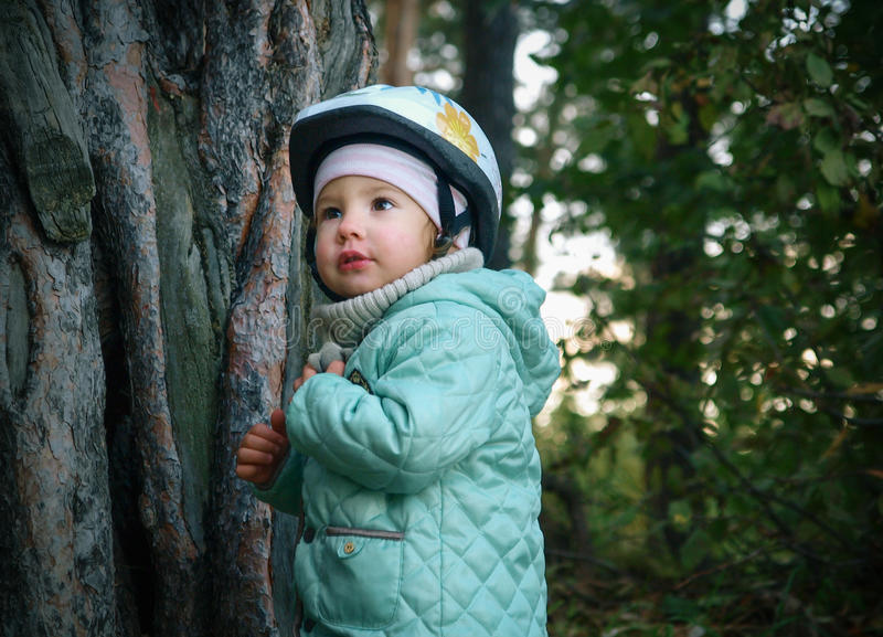 Серьезный маленький ребенок в шлеме смотря вверх стоковые изображения rf