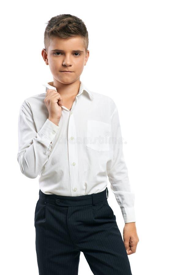 Серьезный мальчик регулирует его воротник стоковое фото rf
