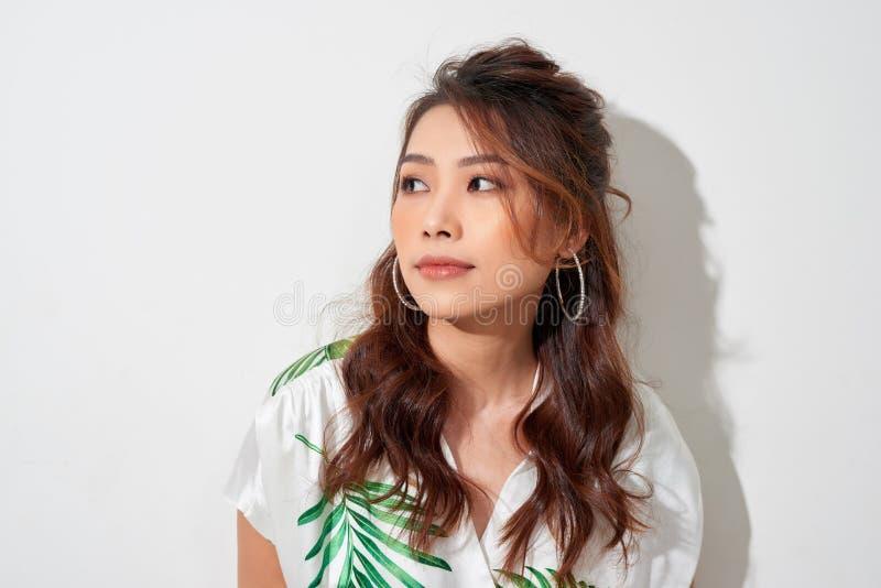 Серьезный молодой азиатский взгляд женщины прочь в тропической рубашке на белой предпосылке стоковая фотография