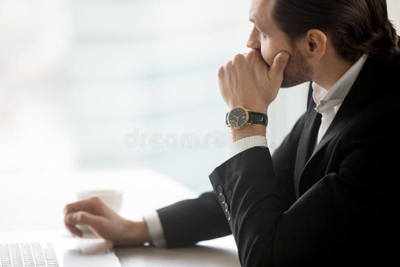 Серьезный молодой бизнесмен в глубокой мысли на рабочем месте в офисе стоковое фото rf