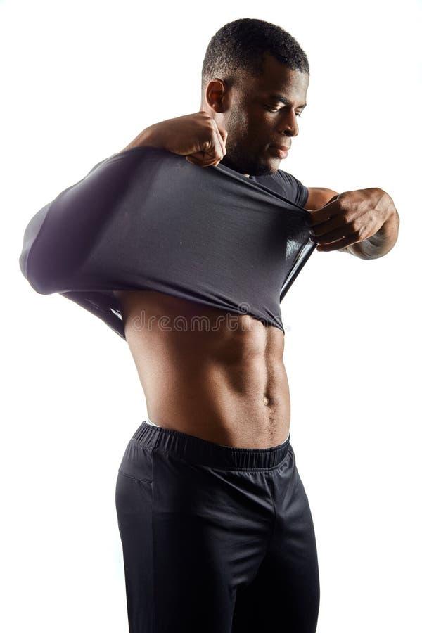 Серьезный молодой сексуальный человек принимает его черную футболку, изолированную на белизне стоковое изображение