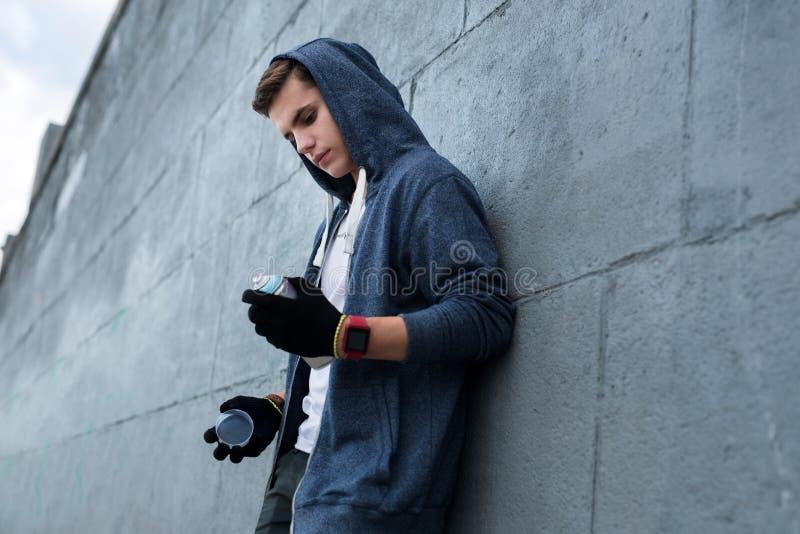 Серьезный молодой человек смотря краску для пульверизатора стоковая фотография