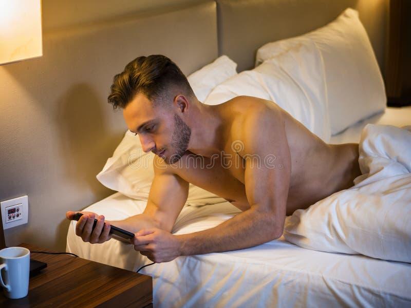 Серьезный молодой человек соединяя телефон к заряжателю стоковое изображение