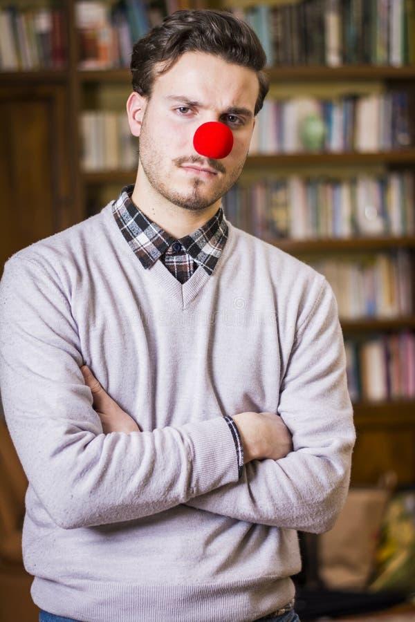 Серьезный молодой человек с красным носом клоуна стоковая фотография rf