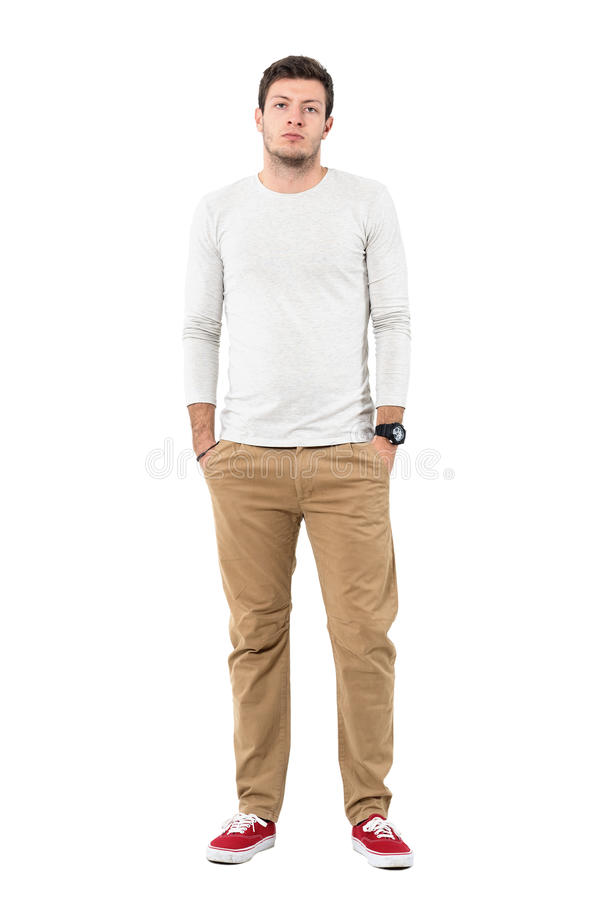 Серьезный молодой человек в красных тапках и ocher брюках с руками в карманн стоковое фото rf