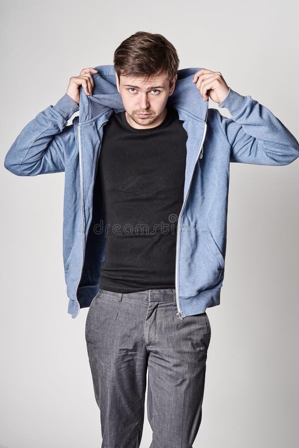 Серьезный молодой человек с светлой бородой в голубом hoodie стоковая фотография