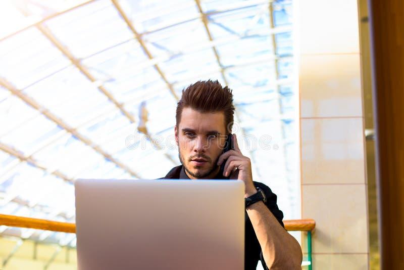 Серьезный мужской главный исполнительный директор вызывая через мобильный телефон, используя netbook стоковое изображение