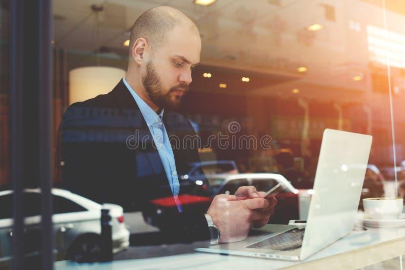 Серьезный мужской главный исполнительный директор отдыхает после videoconferencing через портативный компьютер во время его выезд стоковое изображение rf