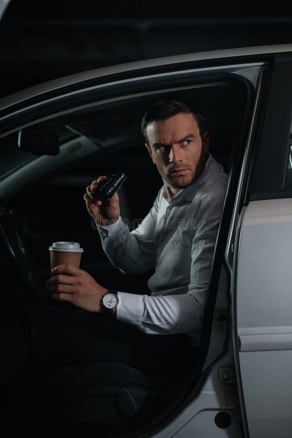 серьезный мужской законспированный агент делая наблюдение биноклями и держа бумажный стаканчик стоковая фотография