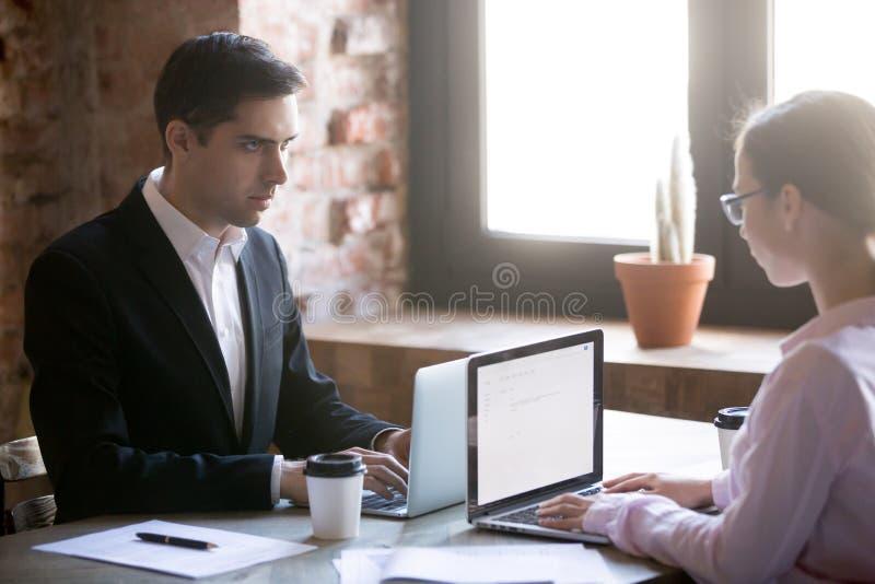 Серьезный мужской и женский смотря один другого борясь для руководства стоковые изображения rf