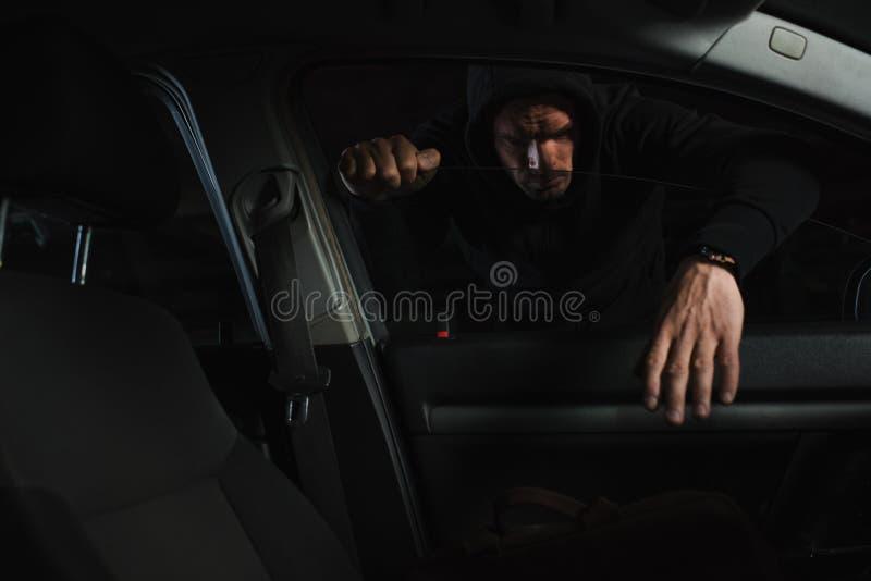 серьезный мужской похититель в черном hoodie крадя сумку стоковая фотография rf