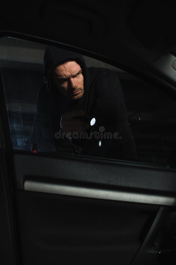 серьезный мужской разбойник в черном hoodie со смотреть электрофонаря стоковые изображения rf