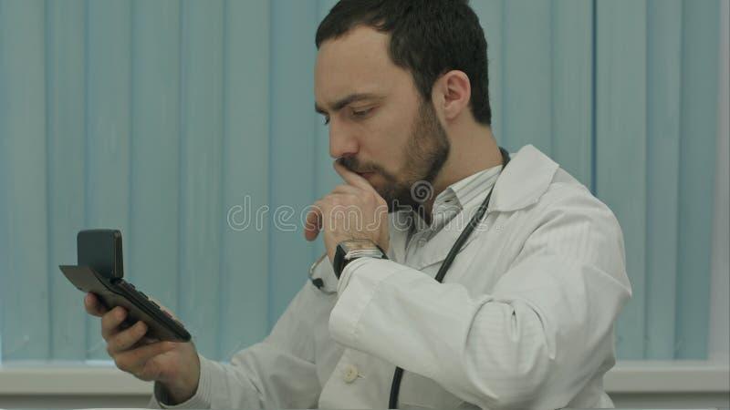 Серьезный мужской фокус доктора на вычислении цен и доходов стоковое изображение