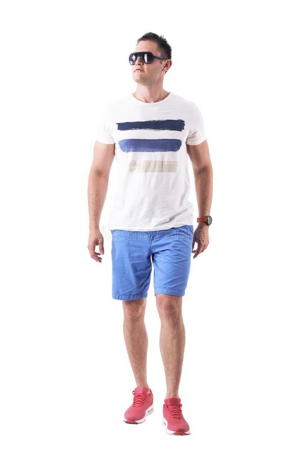 Серьезный мужской человек в футболке лета и шорты с солнечными очками причаливая и смотря вверх с ориентацией стоковое фото rf