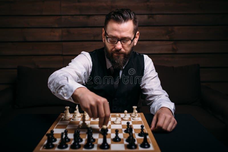 Серьезный мужской шахматист делает движение победы стоковое фото rf