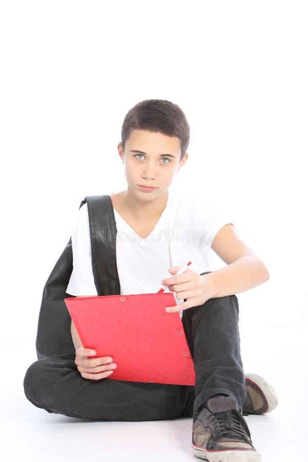 Серьезный подростковый студент сидя на поле стоковая фотография rf
