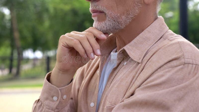 Серьезный постаретый человек с рукой на приобретении планирования подбородка, проблеме здоровья, выборе стоковое изображение rf