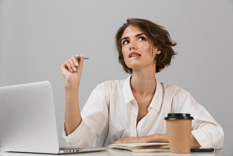 Серьезный представлять бизнес-леди изолированный над серой предпосылкой стены сидя на таблице используя ноутбук стоковые фотографии rf
