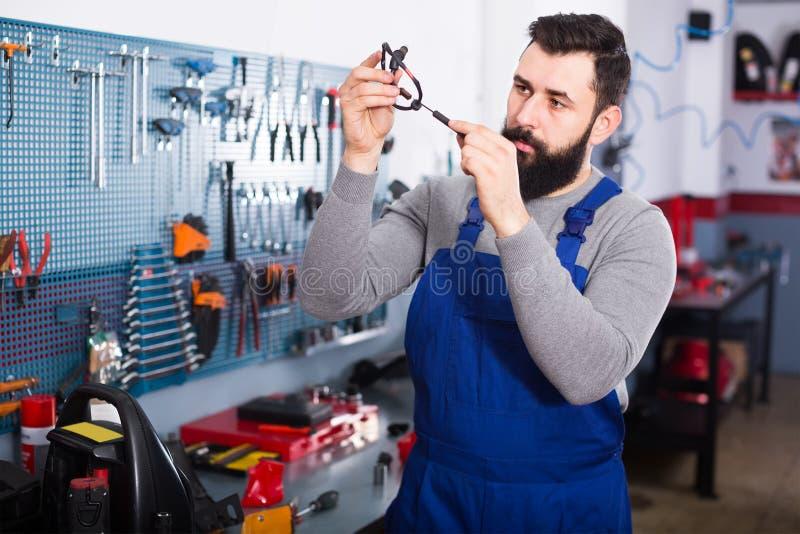 Серьезный работник человека работая на восстанавливать мотоцилк в мастерской стоковые изображения