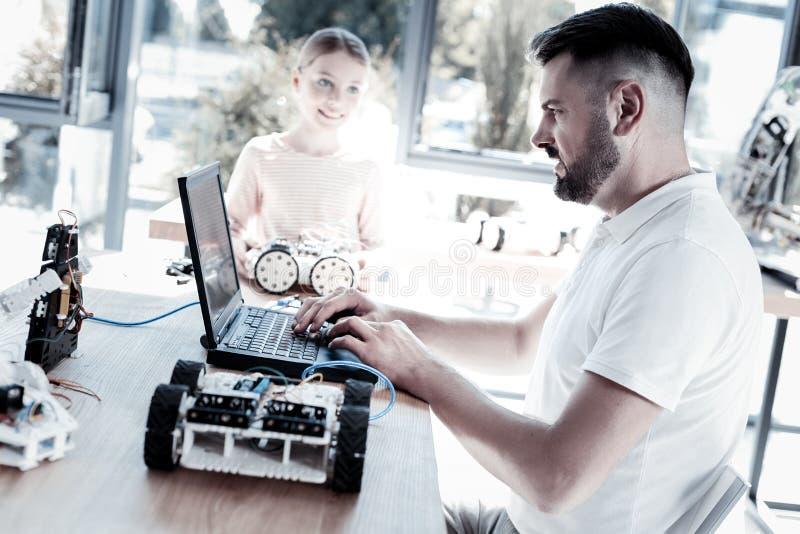 Серьезный робот программирования учителя его студента стоковые фотографии rf