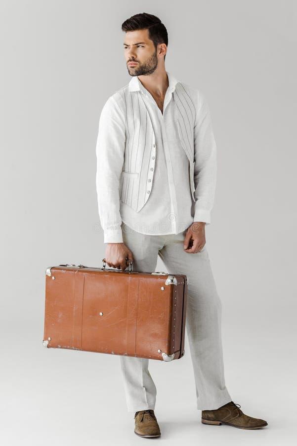 серьезный стильный мужской путешественник в одеждах белья держа винтажный чемодан стоковые изображения rf
