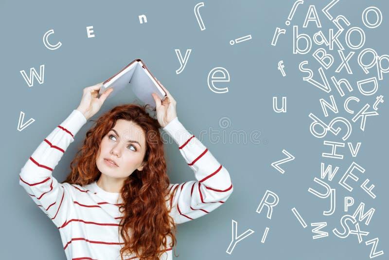 Серьезный студент держа тетрадь и смотря утомленный учить языки стоковая фотография rf