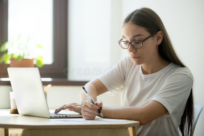 Серьезный студент работая на компьтер-книжке подготавливая для экзаменов стоковая фотография rf