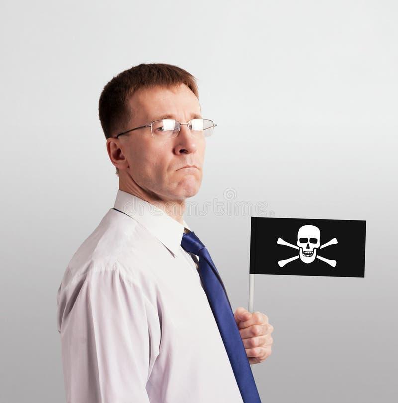 Серьезный твердый человек в связи и стекла с флагом пирата в его руке стоковые изображения