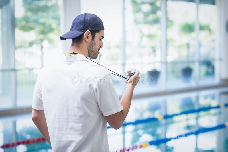 Серьезный тренер смотря секундомер стоковая фотография rf