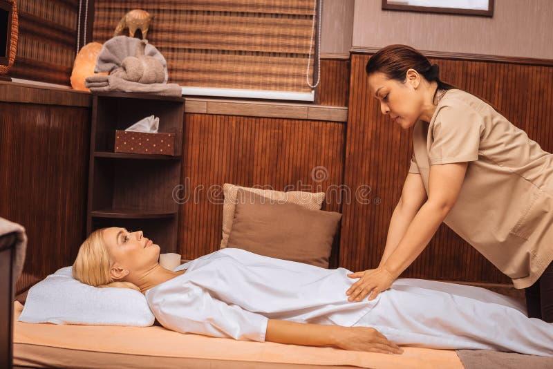 Серьезный умелый азиатский masseuse выполняя массаж стоковые изображения