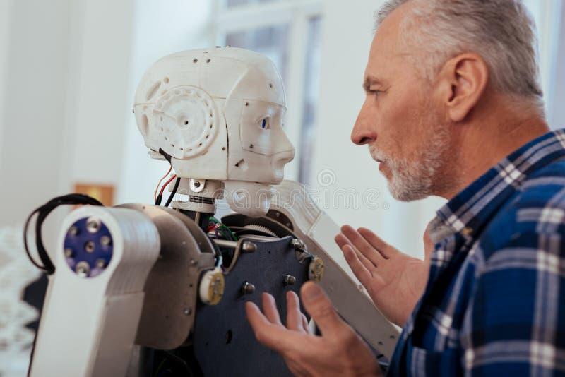 Серьезный умный инженер смотря робот стоковые фотографии rf