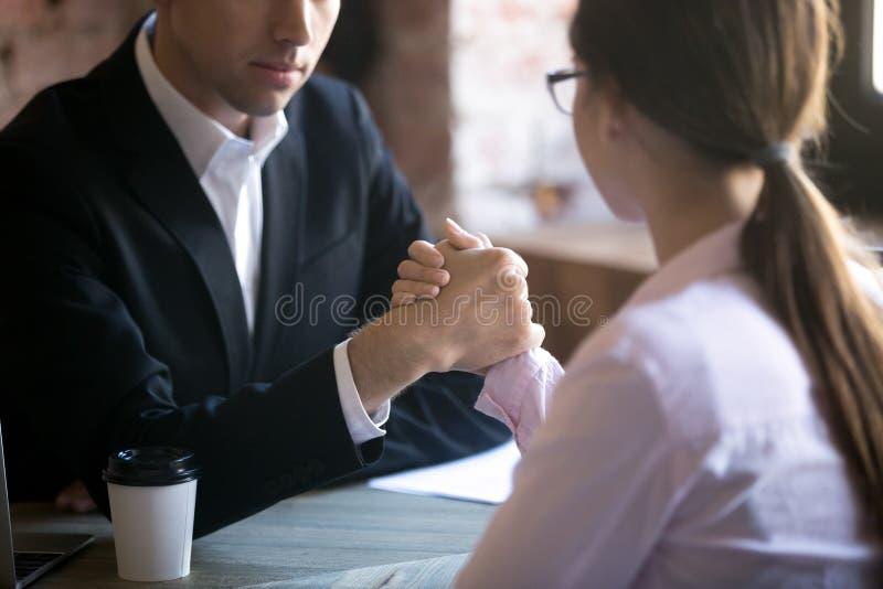 Серьезный человек и женщина armwrestling на рабочем месте стоковое фото