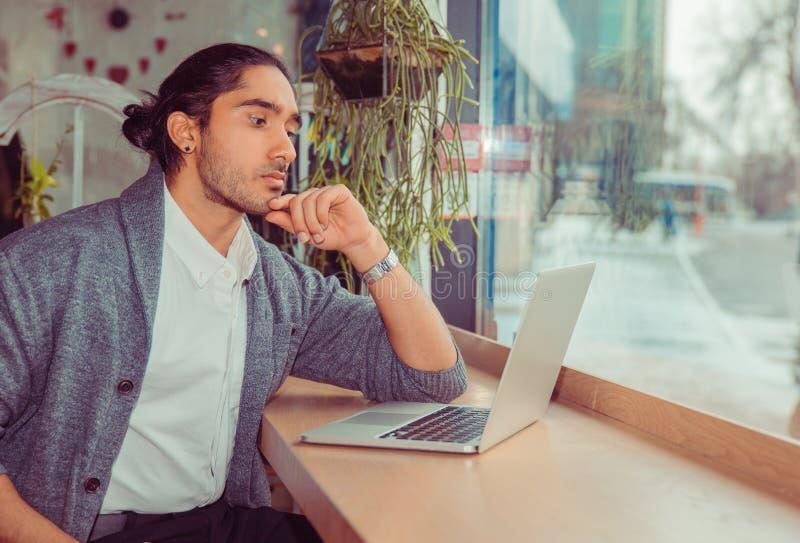 Серьезный человек смотря компьютер стоковая фотография