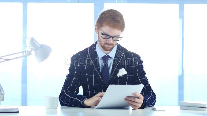 Серьезный человек читая Douments на работе, красных волосах стоковая фотография rf
