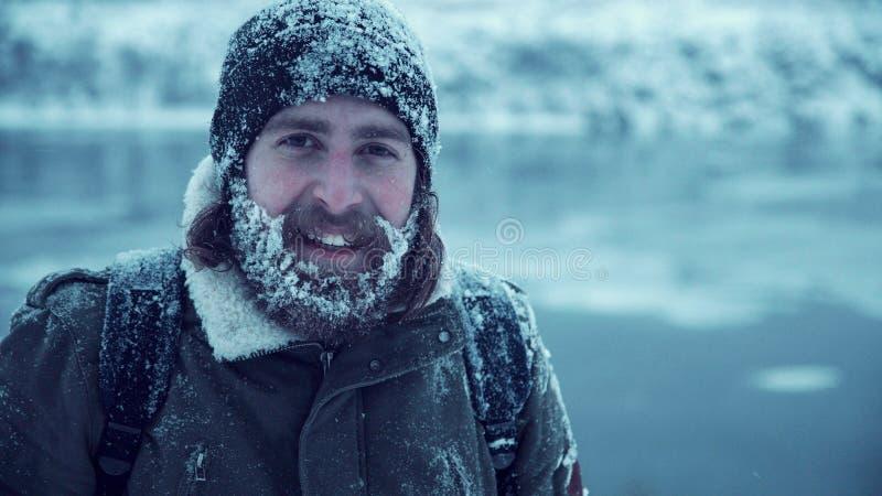 Серьезный человек с бородой в снеге стоковое фото