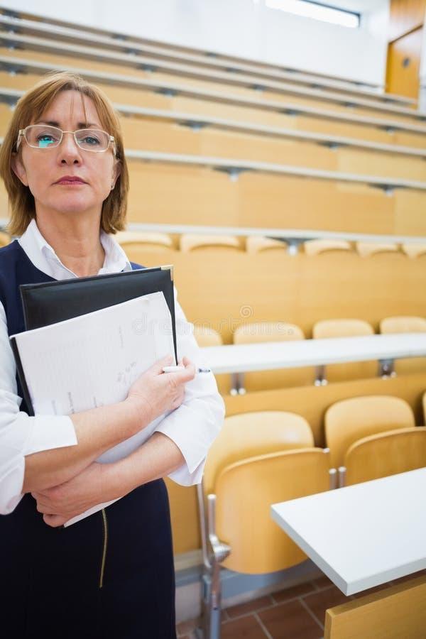 Серьезный элегантный учитель стоя в лекционном зале стоковое изображение rf