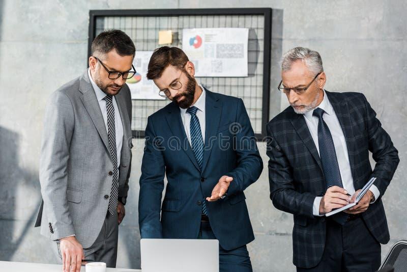 3 серьезных профессиональных бизнесмена смотря ноутбук и обсуждая проект стоковая фотография rf
