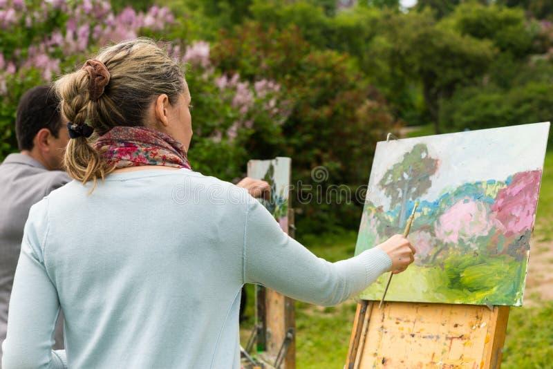 2 серьезных профессиональных художника в процессе outdoors стоковые фотографии rf