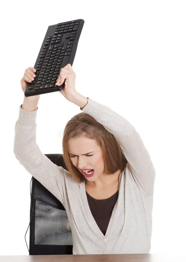 Сердитая женщина бросая клавиатуру ПК стоковая фотография