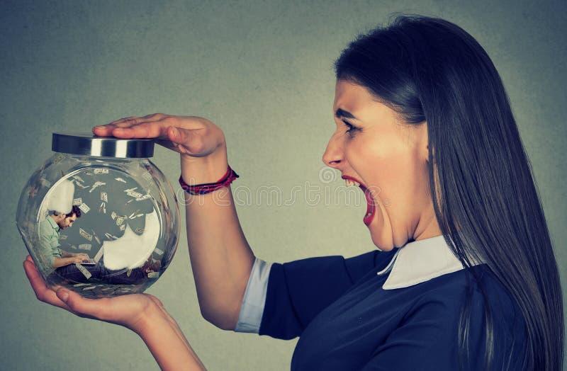 Сердитая женщина держа стеклянный опарник при человек работая на компьтер-книжке поглощенной внутрь стоковые фото