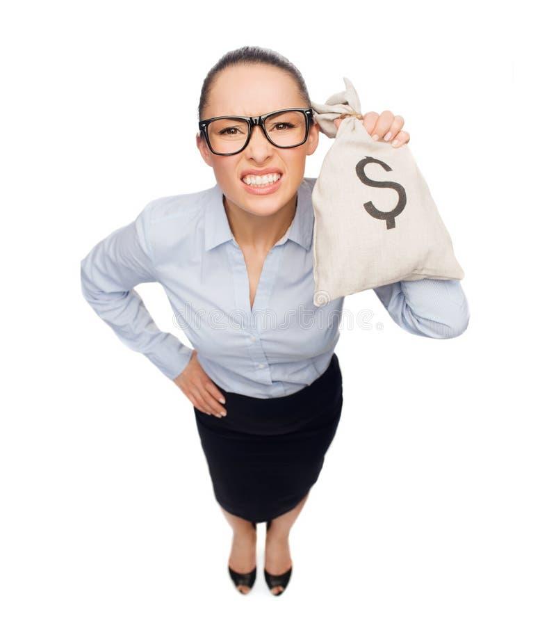 Сердитая коммерсантка держа сумку денег с долларом стоковое фото