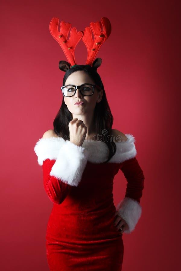 Сердитые молодая женщина с одеждой и стеклами северного оленя и santan в шляпе хелпера santa с фронтом подарочной коробки красной стоковое фото rf