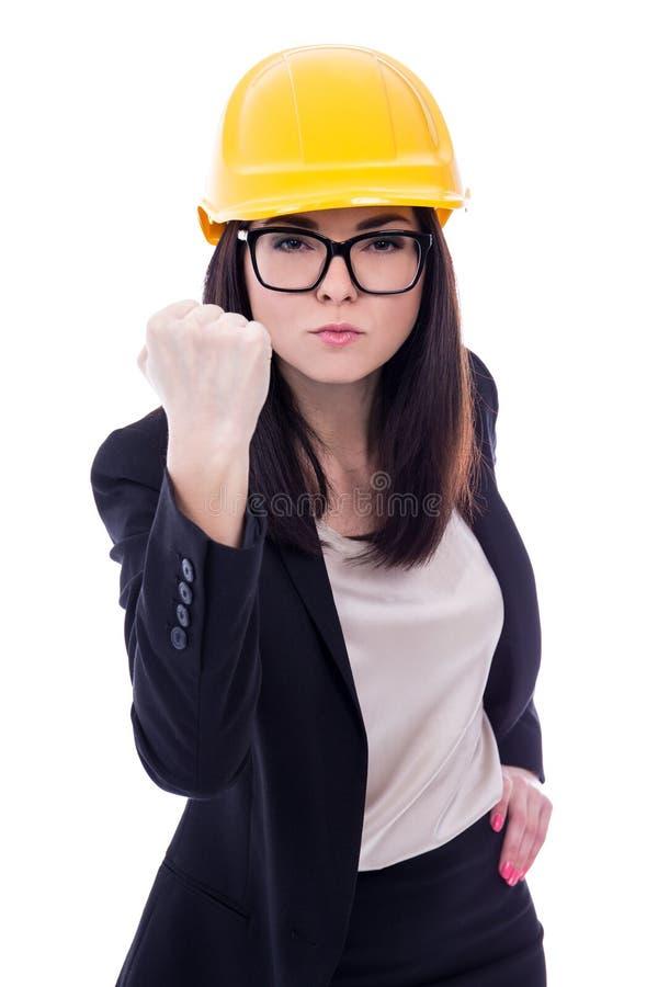 Сердитый архитектор бизнес-леди в желтом шлеме показывая ее кулак стоковая фотография rf