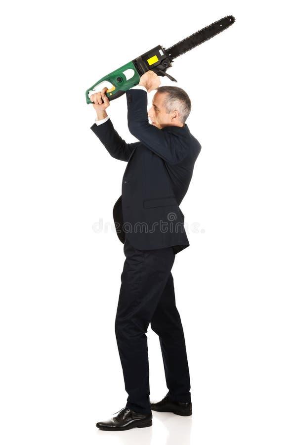 Сердитый бизнесмен с цепной пилой стоковое изображение